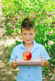 Cute boy is holding books and apple - education concept, outdoor portrait Stock Photo