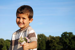 Cute boy holding bunch of flowers Stock Photography