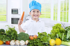 Cute boy holding a carrot in the kitchen Stock Photos