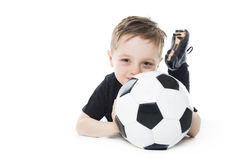 Cute boy is holding a football ball isolated on  white background. Soccer. A Cute boy is holding a football ball isolated on a white background. Soccer Royalty Free Stock Photography