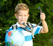 Cute boy is holding globe. Education concept Stock Photos