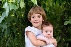 Cute boy holding his baby sister outside in a park. Cute boy holding his sweet baby sister outside in a park stock photography