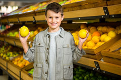 Cute boy holding lemons Royalty Free Stock Image