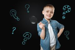 Cute boy holding a magnifying glass and looking glad. Future scientist. Cheerful little boy standing with a magnifying glass in his hand and thinking about royalty free stock photos