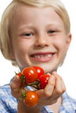 Cute boy holding out bunch of tomatoes Stock Photo