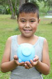 Cute boy holding piggy bank Stock Images