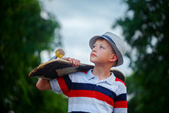 Cute boy holding skateboard  in hand outdoors.Wearing cap and stylish clothes. Looking away Stock Photo