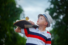 Cute boy holding skateboard in hand outdoors. Cute boy holding skateboard  in hand outdoors.Wearing cap and stylish clothes.  Looking away Royalty Free Stock Photo