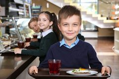Cute boy holding tray with healthy food in canteen. Cute boy holding tray with healthy food in school canteen stock photos