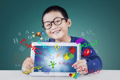 Cute boy holds tablet for studying Stock Photo