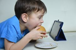 Cute boy at home on the couch, eating a hamburger and looking at the tablet, watching cartoons or talking with friends Royalty Free Stock Photography