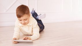 Cute boy playing Computer tablet and chat on floor royalty free stock images