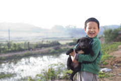 Cute boy hug black dog with smile Stock Photos