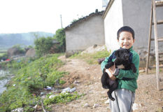 Cute boy hug black dog with smile Stock Images