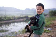 Cute boy hug black dog with smile Royalty Free Stock Images