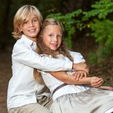 Cute boy hugging girlfriend in park. Royalty Free Stock Image