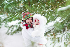 Cute boy hugging his baby sister in a winter park Royalty Free Stock Image