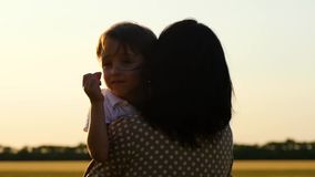 Cute boy hugging his mom. Close-up of a child`s face. Happy family at sunset.