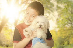 Cute boy hugging his puppy at the park Stock Photo