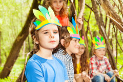 Cute boy in Injun`s headdress playing with friends Royalty Free Stock Image