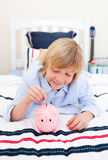 Cute boy inserting a coin in a piggy-bank Royalty Free Stock Photography