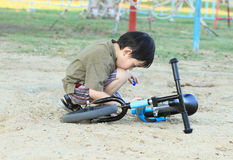 Cute boy interesting in his bicycle Royalty Free Stock Photography