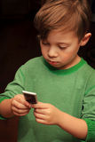 Cute Boy with iPod. Cute young 6yr old boy with brown hair wearing green shirt staring intently on an iPod, dark background Stock Photos