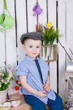 Cute boy in jeans suit and a cap on his headsitting on a bright background juicy stock photography