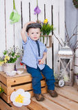 Cute boy in jeans suit and a cap on his headsitting on a bright background juicy stock photo