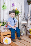 Cute boy in jeans suit and a cap on his headsitting on a bright background juicy stock photos