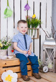 Cute boy in jeans suit sitting on a bright background juicy stock images