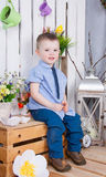 Cute boy in jeans suit sitting on a bright background juicy royalty free stock images