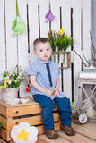 Cute boy in jeans suit sitting on a bright background juicy royalty free stock photos