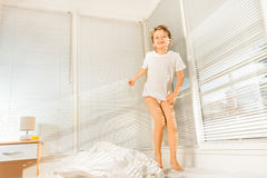 Cute boy jumping on his bed in sunny morning Royalty Free Stock Images