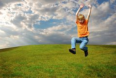 Cute boy jumping on plain meadow Stock Images