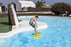Cute boy jumping in the pool. Cute boy jumping in the outdoor pool Stock Image