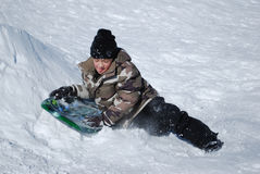 Cute boy jumping a sled with copyspace. Royalty Free Stock Image