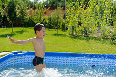Cute boy jumping in swimming pool. Cute boy jumpong in a pool at the garden Stock Image