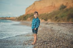 Cute boy kid child wearing stylish shirt and blue jeans barefoot posing running on stone beach with gorgeous ocean sea landscape s stock photo