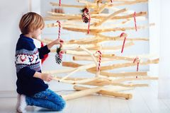 Cute boy, kid decorate handcrafted christmas tree made of driftwood at home Royalty Free Stock Image