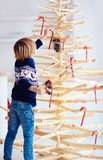 Cute boy, kid decorate handcrafted christmas tree made of driftwood at home Stock Images