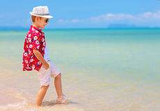 Cute boy, kid playing in waves on summer beach Stock Image