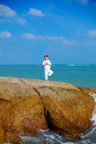 Cute boy kid  practicing yoga on the rock in the sea Royalty Free Stock Image