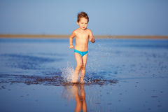 Cute boy kid running the lake Royalty Free Stock Photography