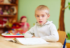 Cute boy, kid with special needs learning in rehabilitation center stock images