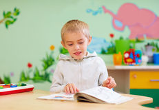 Cute boy, kid with special needs looking at a book, in rehabilitation center stock images