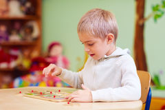 Cute boy, kid with special needs solving a puzzle in rehabilitation center stock images