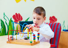 Cute boy, kid in wheelchair solving logical puzzle in rehabilitation center for children with special needs Stock Images