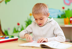 Free Cute Boy, Kid With Special Needs Looking At A Book, In Rehabilitation Center Royalty Free Stock Image - 80642846