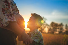 Cute boy kissing his mothers pregnant belly. Cute boy kissing and listening his mothers pregnant mehandi pattern ornament belly on sunset nature landscape royalty free stock images